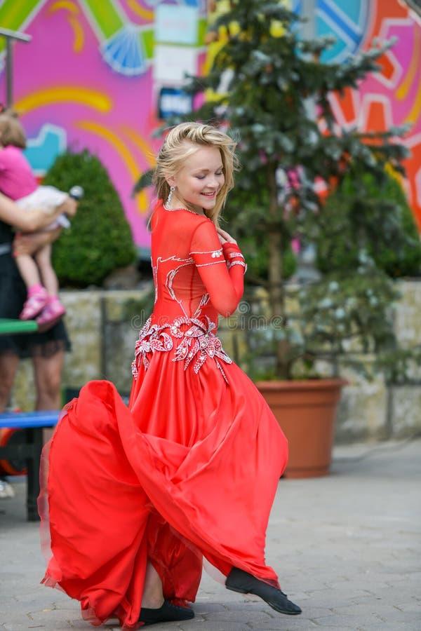 Bailarín hermoso en un vestido rojo Baile hermoso de la chica joven en un vestido rojo Danza en público El niño talentoso hace ba fotografía de archivo