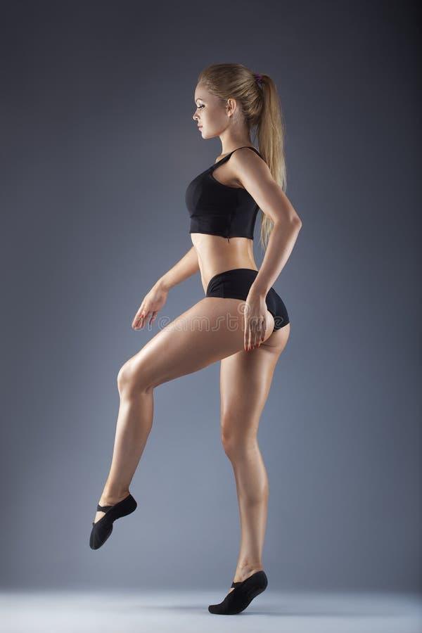 Bailarín hermoso joven que presenta en un fondo del estudio foto de archivo