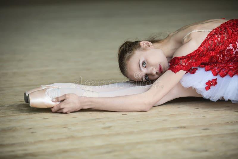 Bailarín joven encantador que hace estirar inclinado encima, mirando t fotos de archivo libres de regalías