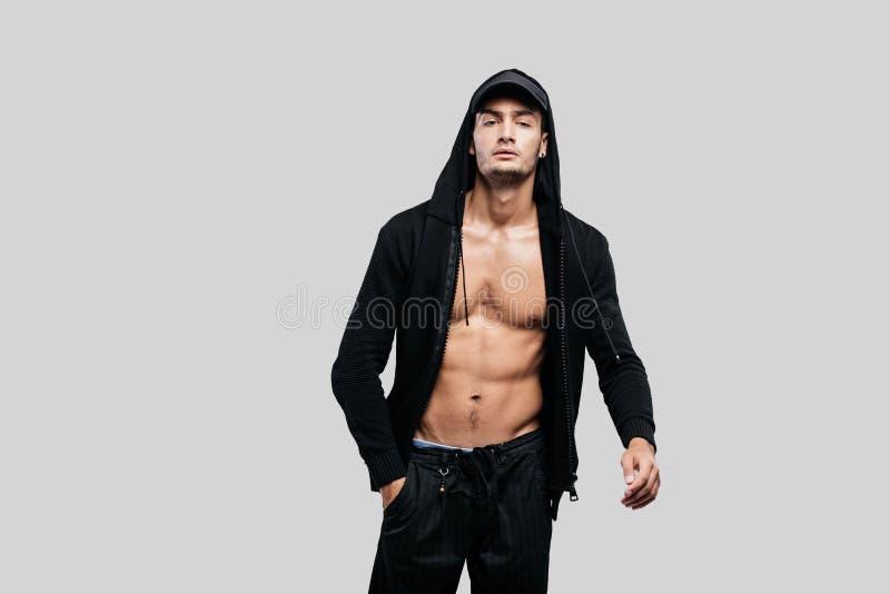 Bailarín joven hermoso vestido en una camiseta en un torso desnudo con una capilla en el casquillo y soportes negros de los panta foto de archivo