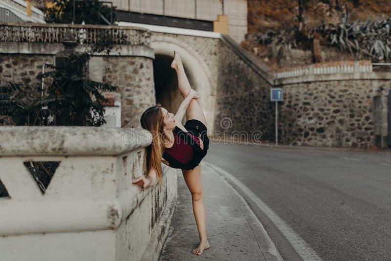 Bailarín que aumenta la pierna mientras que realiza danza clásica en un camino imagen de archivo libre de regalías