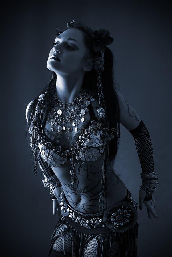 Bailarín tribal en obscuridad azul fotografía de archivo