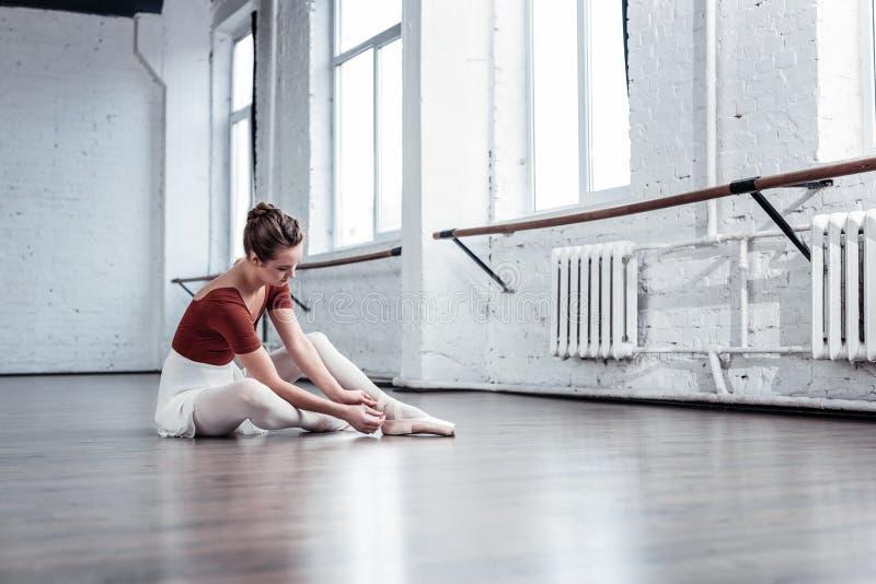 Bailarina agradável atrativa que senta-se no assoalho no estúdio da dança foto de stock royalty free