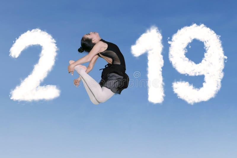 Bailarina asiática que salta con el número 2019 fotos de archivo