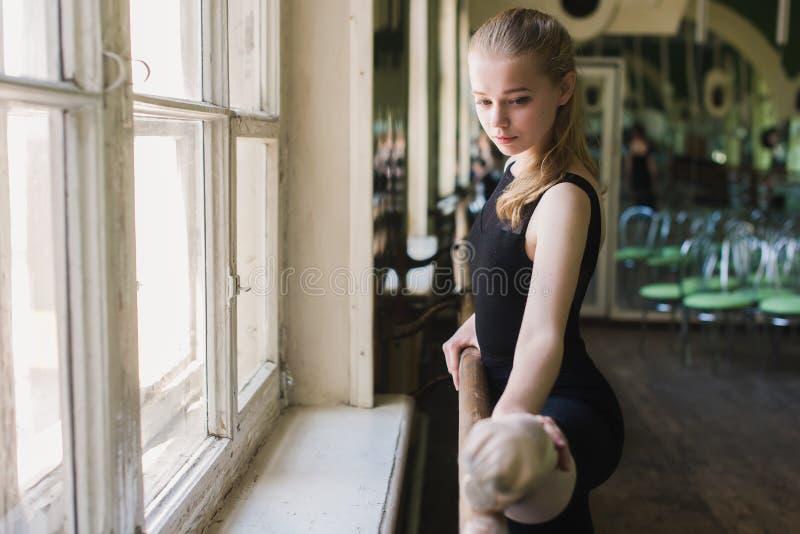 Bailarina atrativa que aquece-se na classe do bailado fotografia de stock