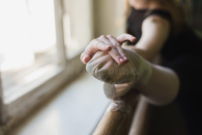 Bailarina atrativa que aquece-se na classe do bailado fotografia de stock royalty free