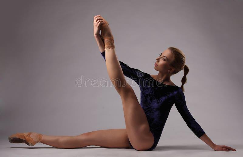 Bailarina bonita com corpo perfeito no equipamento azul no estúdio imagens de stock