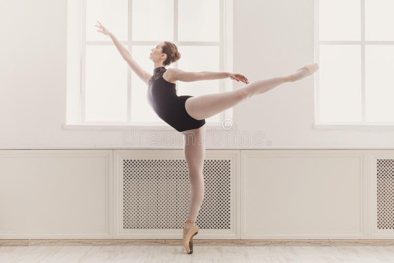 Bailarina bonita na posição de bailado do arabesque fotografia de stock