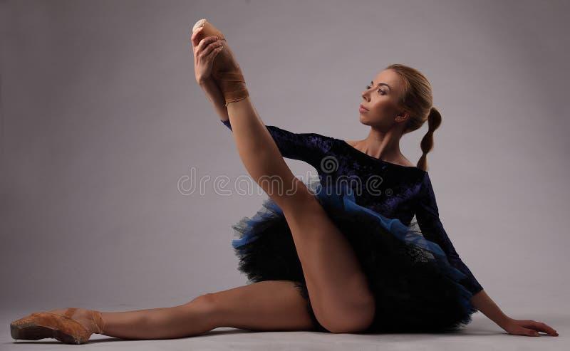 A bailarina bonita no equipamento azul no estúdio senta-se no assoalho e guarda-se seu pé fotografia de stock royalty free