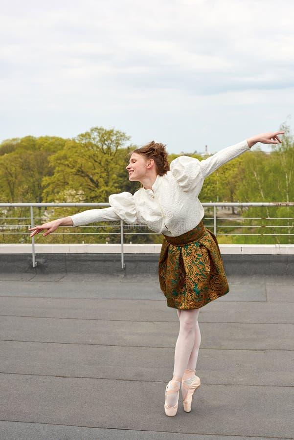 Bailarina caucásica de la moda que salta en el tejado imágenes de archivo libres de regalías