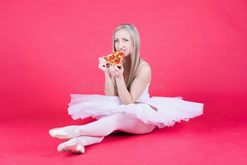 A bailarina consideravelmente loura bonita da bailarina está feliz comer um piz fotos de stock royalty free