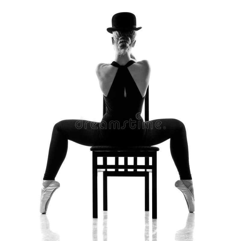 Bailarina consideravelmente nova que senta-se na cadeira. Vista traseira foto de stock