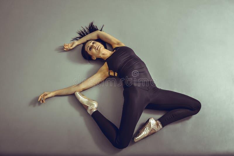 Bailarina da jovem mulher que encontra-se no assoalho sem sentimentos no estúdio do bailado, vista de cima de foto de stock