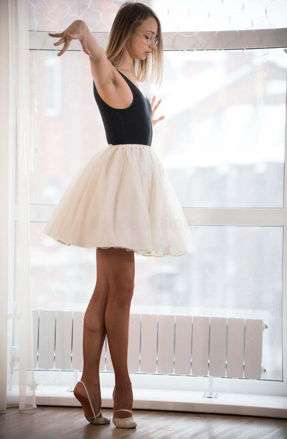 A bailarina da menina nos vidros está perto da janela na ponta do pé no estúdio imagem de stock royalty free