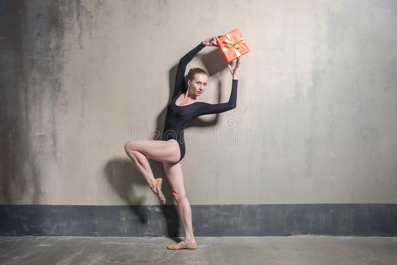 Bailarina de la elegancia que sostiene la caja de regalo sobre la cabeza fotos de archivo libres de regalías