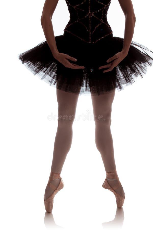Bailarina de la mujer en el tutú negro que presenta en el fondo blanco foto de archivo