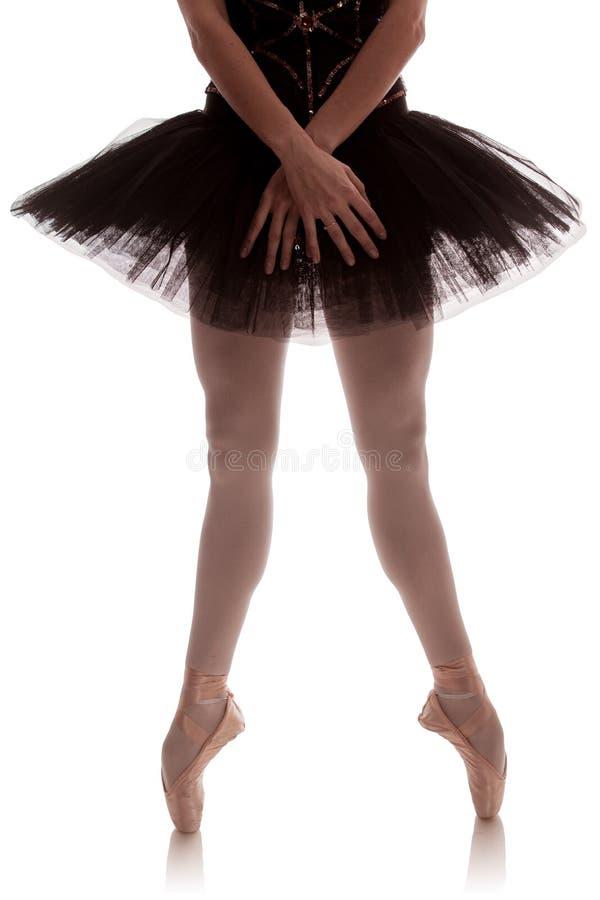 Bailarina de la mujer en el tutú negro que presenta en el fondo blanco imágenes de archivo libres de regalías