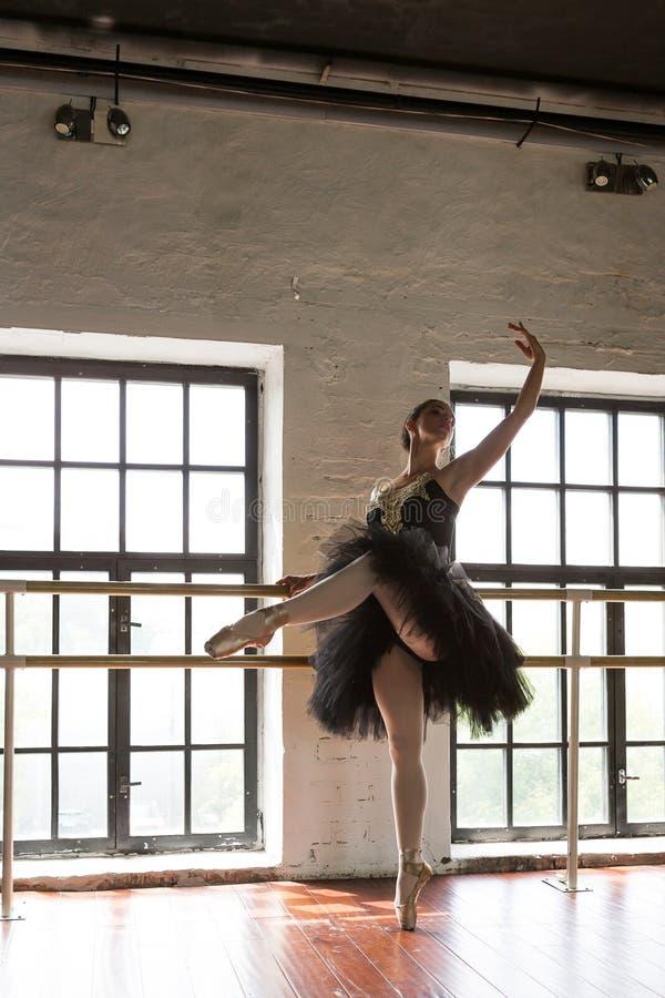 Bailarina del ensayo en el pasillo Piso de madera, ventanas grandes Bailarina hermosa en el cuarto del ensayo imagenes de archivo