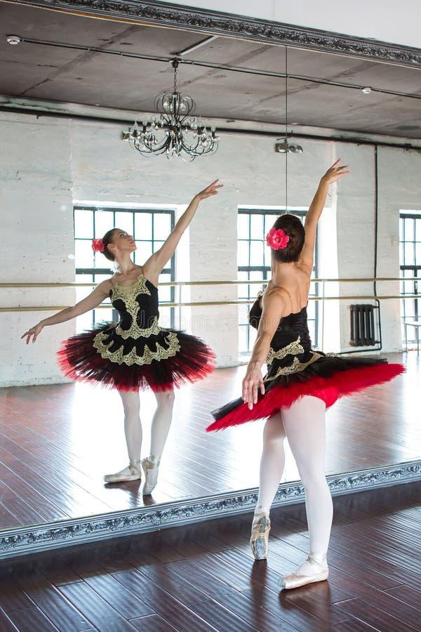 Bailarina del ensayo en el pasillo Sitio blanco ligero, piso de madera, espejos grandes Bailarina reflejada en el espejo imagen de archivo libre de regalías