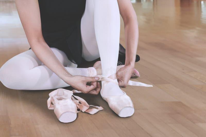 Bailarina desconhecida que amarra suas sapatas na classe do bailado foto de stock