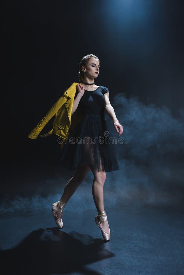 bailarina elegante à moda em sapatas do pointe e no casaco de cabedal preto do tutu e o amarelo no estúdio fotos de stock