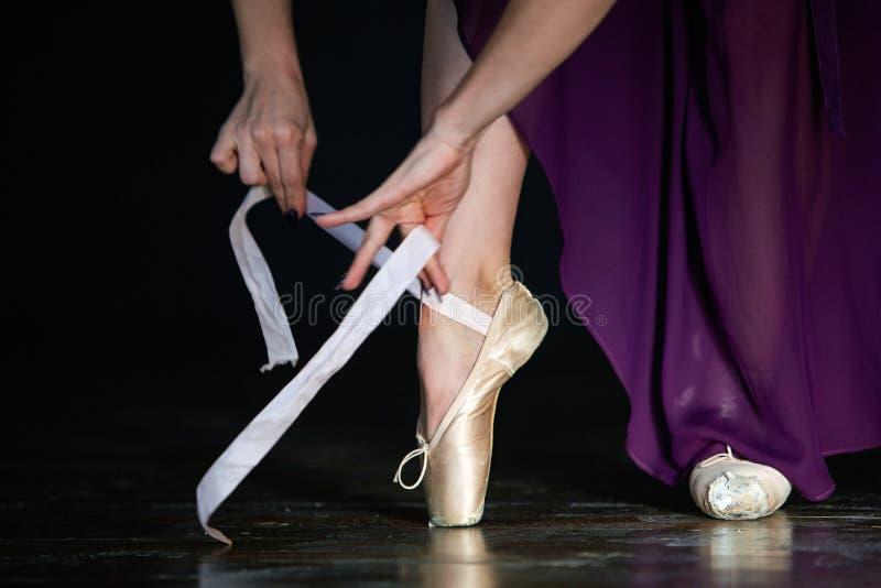 A bailarina elegante está levantando no estúdio no fundo escuro na baixa chave imagens de stock royalty free