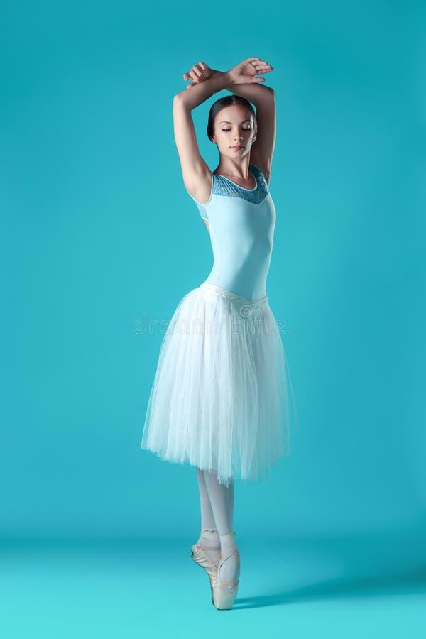 Bailarina en el vestido blanco que presenta en los dedos del pie, fondo del estudio imagen de archivo libre de regalías