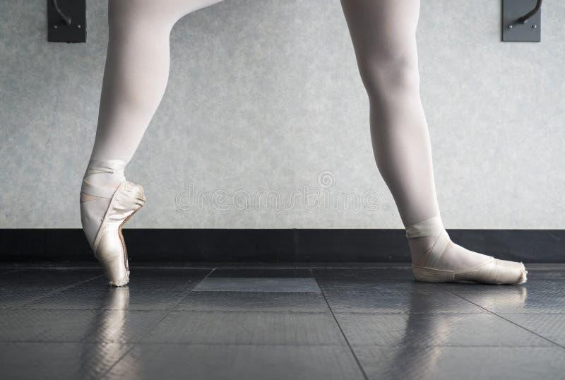 Bailarina en la clase del ballet que calienta sus zapatos del pointe, deslizadores del ballet en la barra fotos de archivo libres de regalías