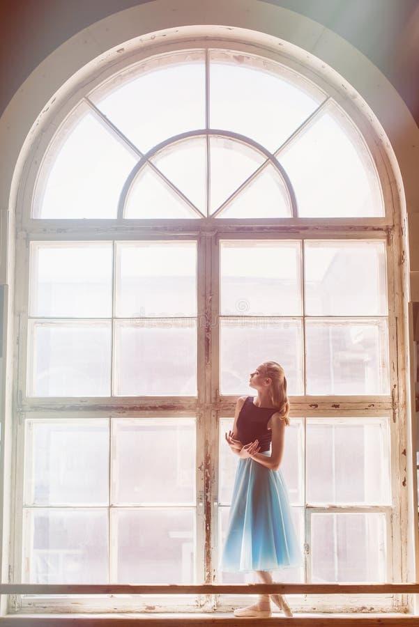 A bailarina está levantando na frente de uma grande janela fotos de stock