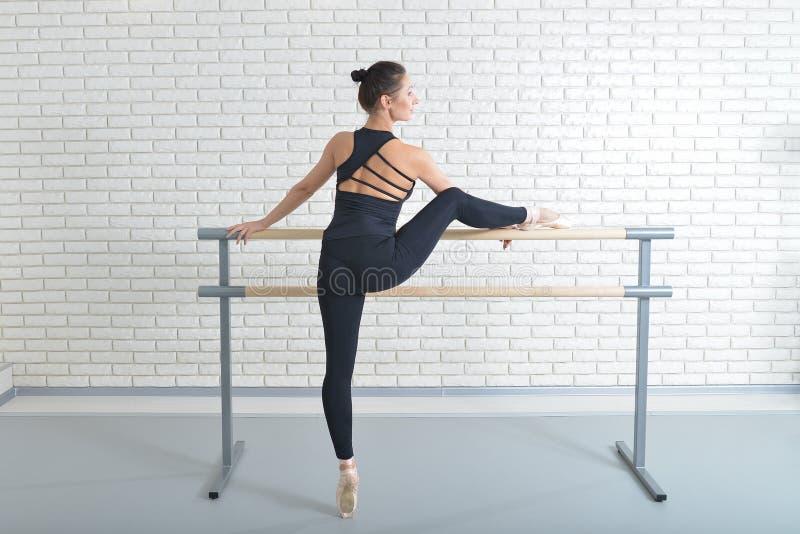 A bailarina estica-se perto da barra no estúdio do bailado, retrato completo do comprimento imagem de stock