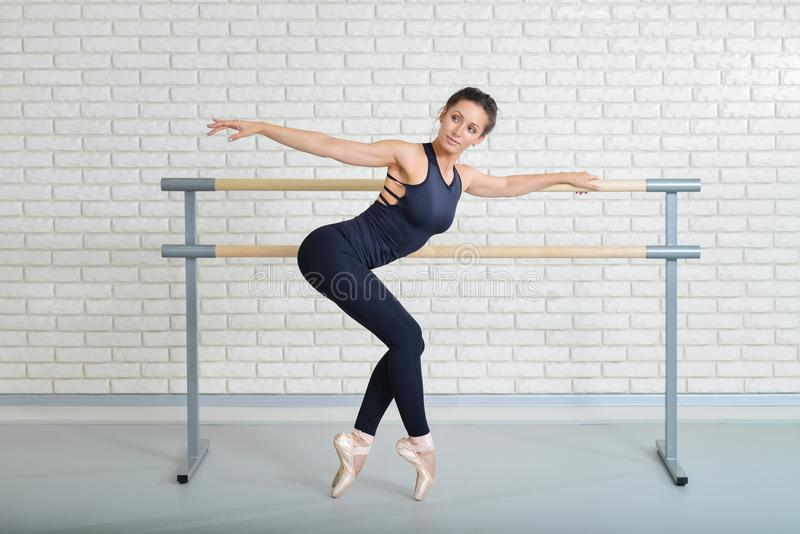 A bailarina estica-se perto da barra no estúdio do bailado, retrato completo do comprimento foto de stock royalty free