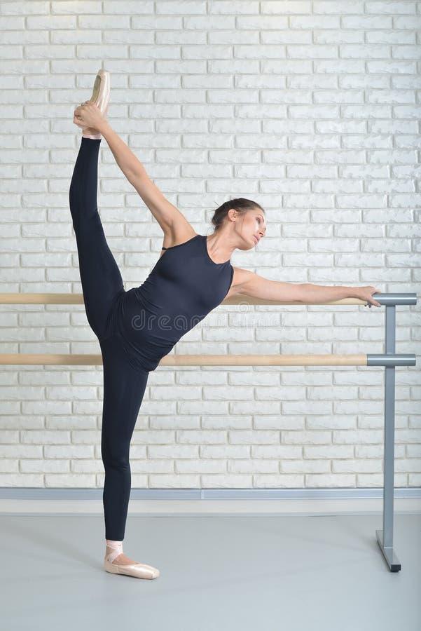 A bailarina estica-se perto da barra no estúdio do bailado, retrato completo do comprimento, executando a guita foto de stock royalty free