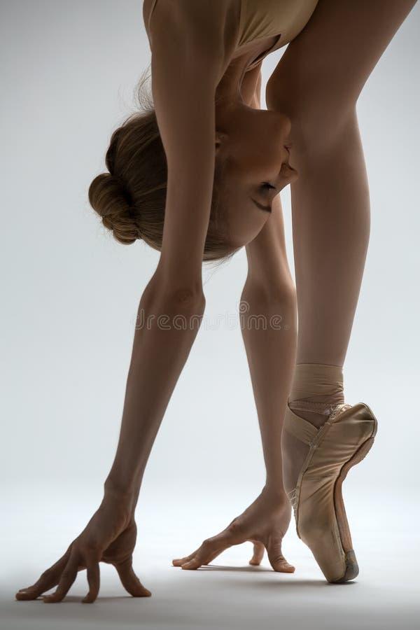 A bailarina frágil toma uma inclinação profunda para a frente fotografia de stock royalty free