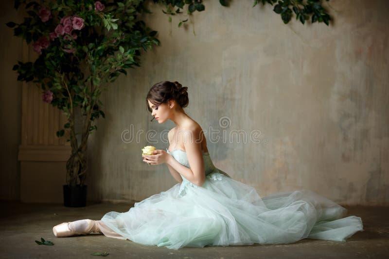 A bailarina graciosa bonita da menina em um vestido do ar e o pointe sentam-se fotos de stock