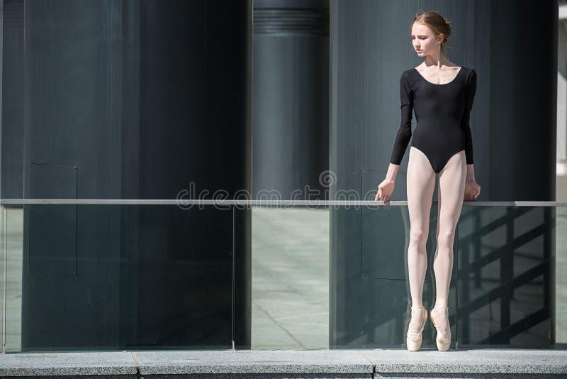 Bailarina graciosa nova no maiô preto sobre foto de stock royalty free