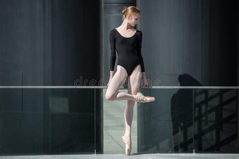 Bailarina graciosa nova no maiô preto sobre imagem de stock