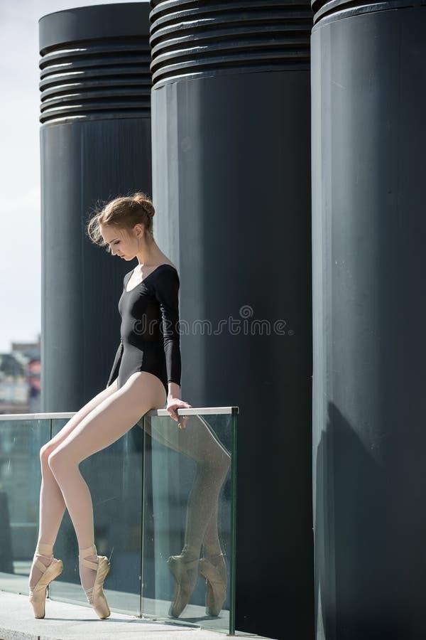 Bailarina graciosa nova no maiô preto sobre fotografia de stock