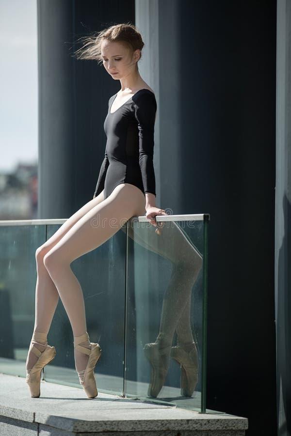 Bailarina graciosa nova no maiô preto sobre fotos de stock