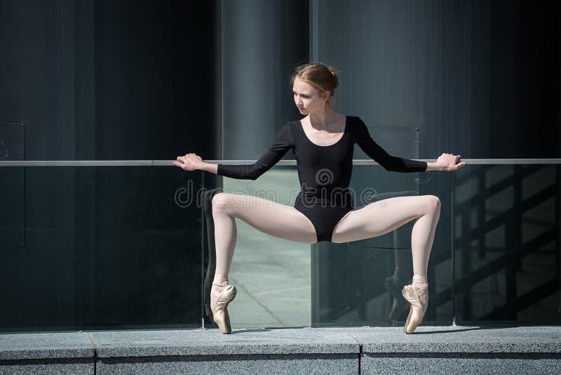 Bailarina graciosa nova no maiô preto sobre imagens de stock
