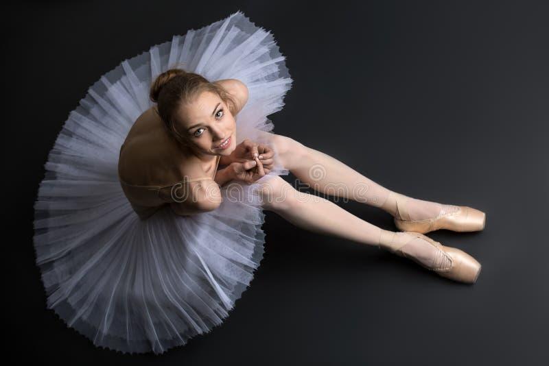 Bailarina graciosa que senta-se no assoalho fotografia de stock royalty free