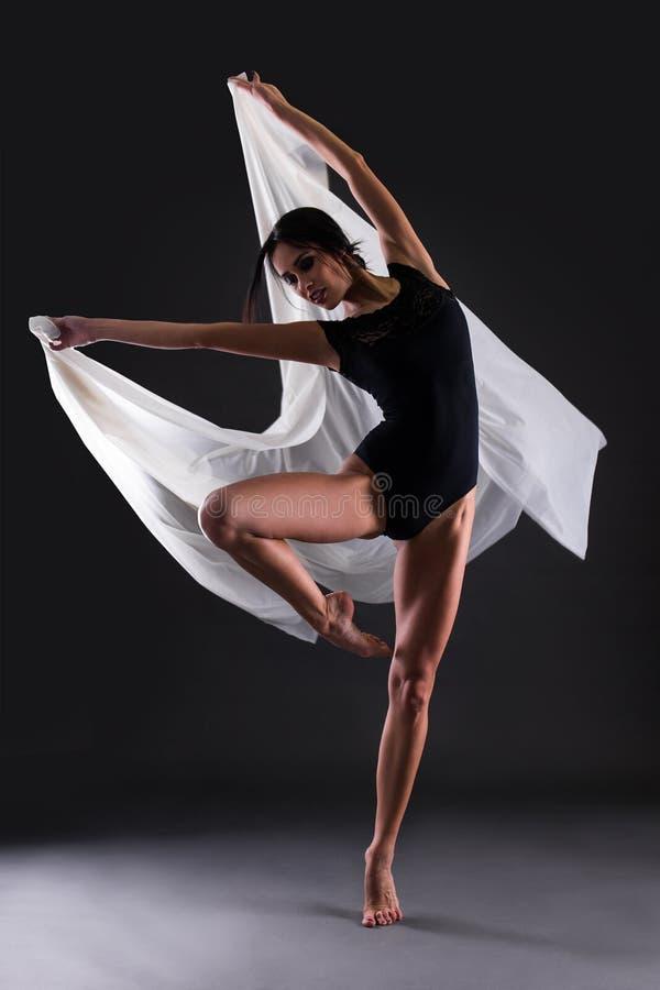 Bailarina hermosa joven de la mujer en el traje del cuerpo negro que baila encima fotos de archivo