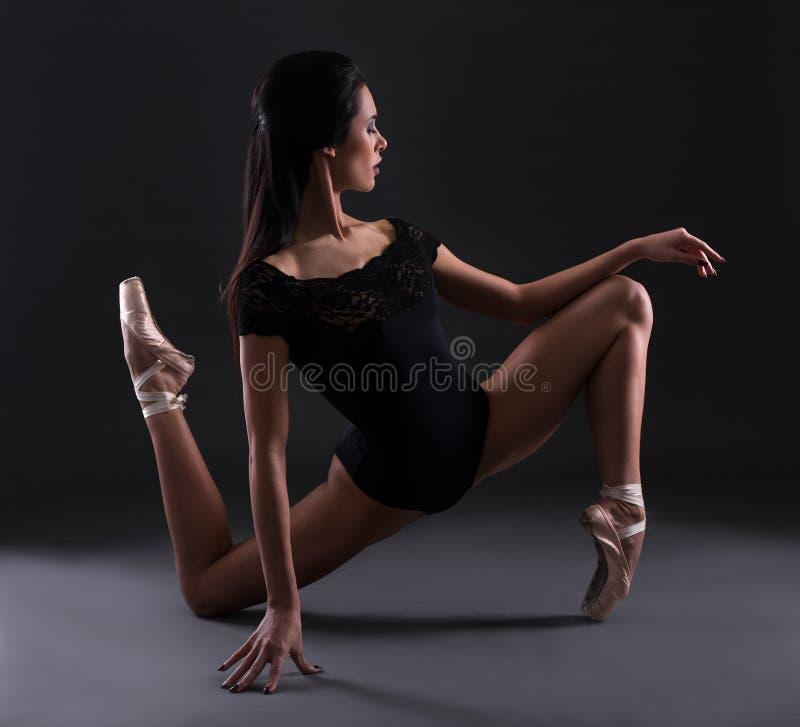 Bailarina hermosa joven de la mujer en el traje del cuerpo negro que presenta sobre b imagenes de archivo