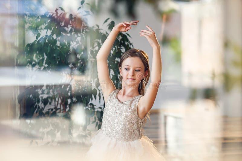 Bailarina joven en los zapatos del tutú y de ballet del pointe que practican movimientos de la danza en el pasillo de baile foto de archivo libre de regalías