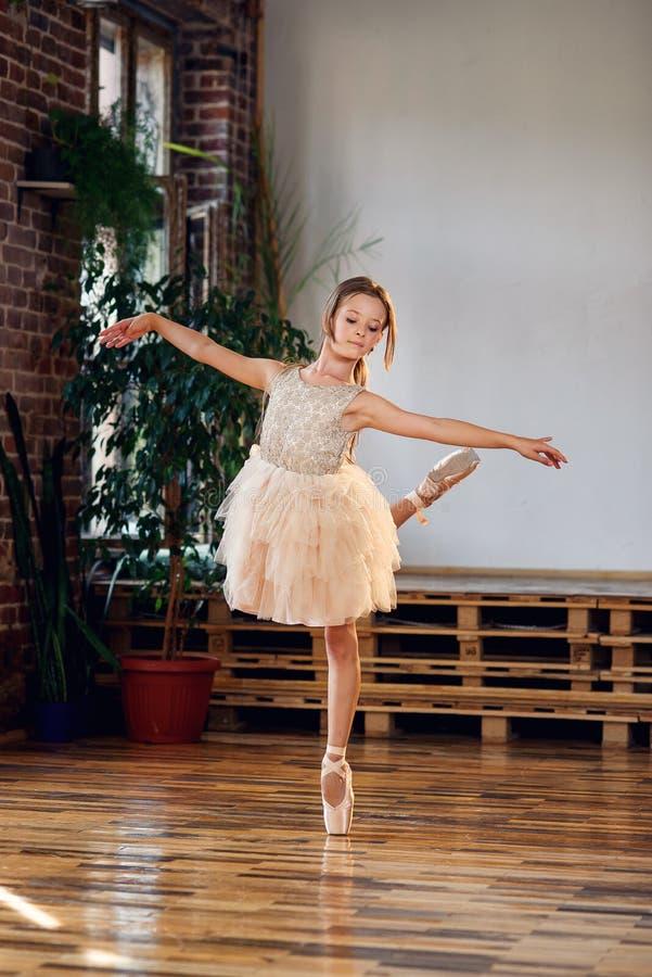 Bailarina joven en los zapatos del tutú y de ballet del pointe que practican movimientos de la danza en el pasillo de baile fotografía de archivo