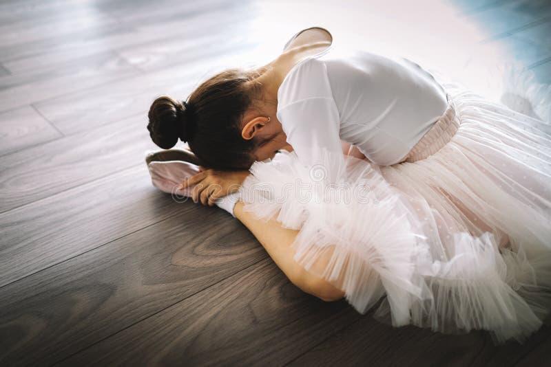 Bailarina joven en movimientos practicantes de la danza del tutú Chica joven en vestido del ballet en escuela de danza foto de archivo libre de regalías