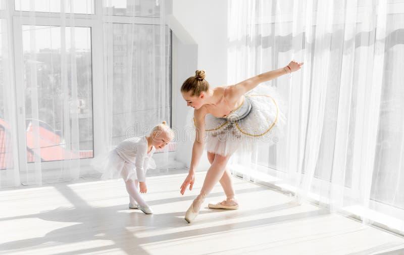 Bailarina lindo nova com sua dança pequena da filha no estúdio foto de stock royalty free