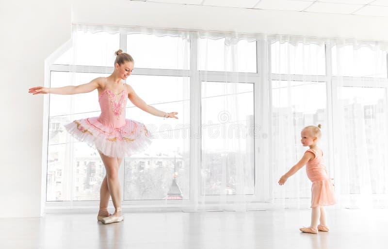 Bailarina lindo nova com sua dança pequena da filha no estúdio foto de stock
