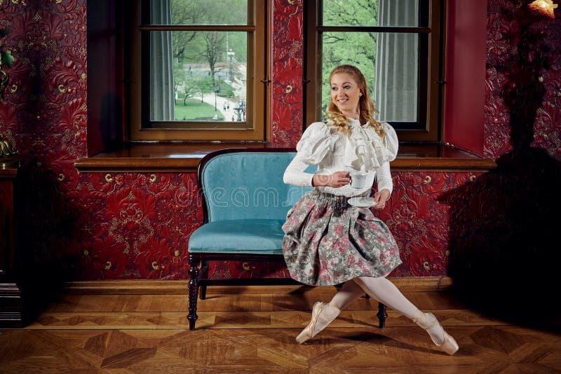 A bailarina loura na forma veste o assento no sofá e beber o chá fotografia de stock