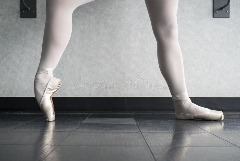 Bailarina na classe do bailado que aquece suas sapatas do pointe, deslizadores do bailado na barra fotos de stock royalty free