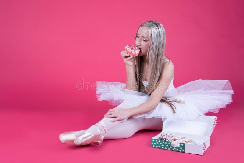 Bailarina na saia do tutu que come uma filhós imagem de stock royalty free